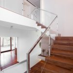 Image of solid wooden stairs with elegant glass balustrade